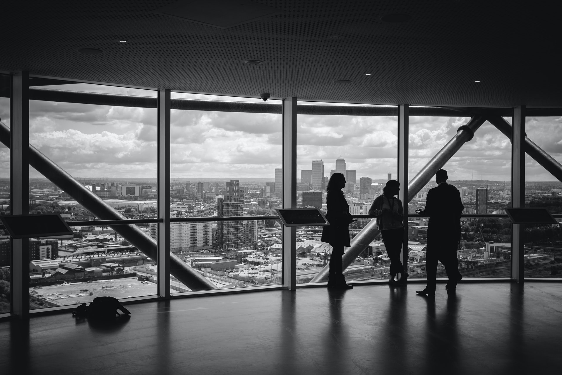 a black and white picture managers in front of a glass overlooking the skyline of a city, pondering the benefits of reading corporate fiction