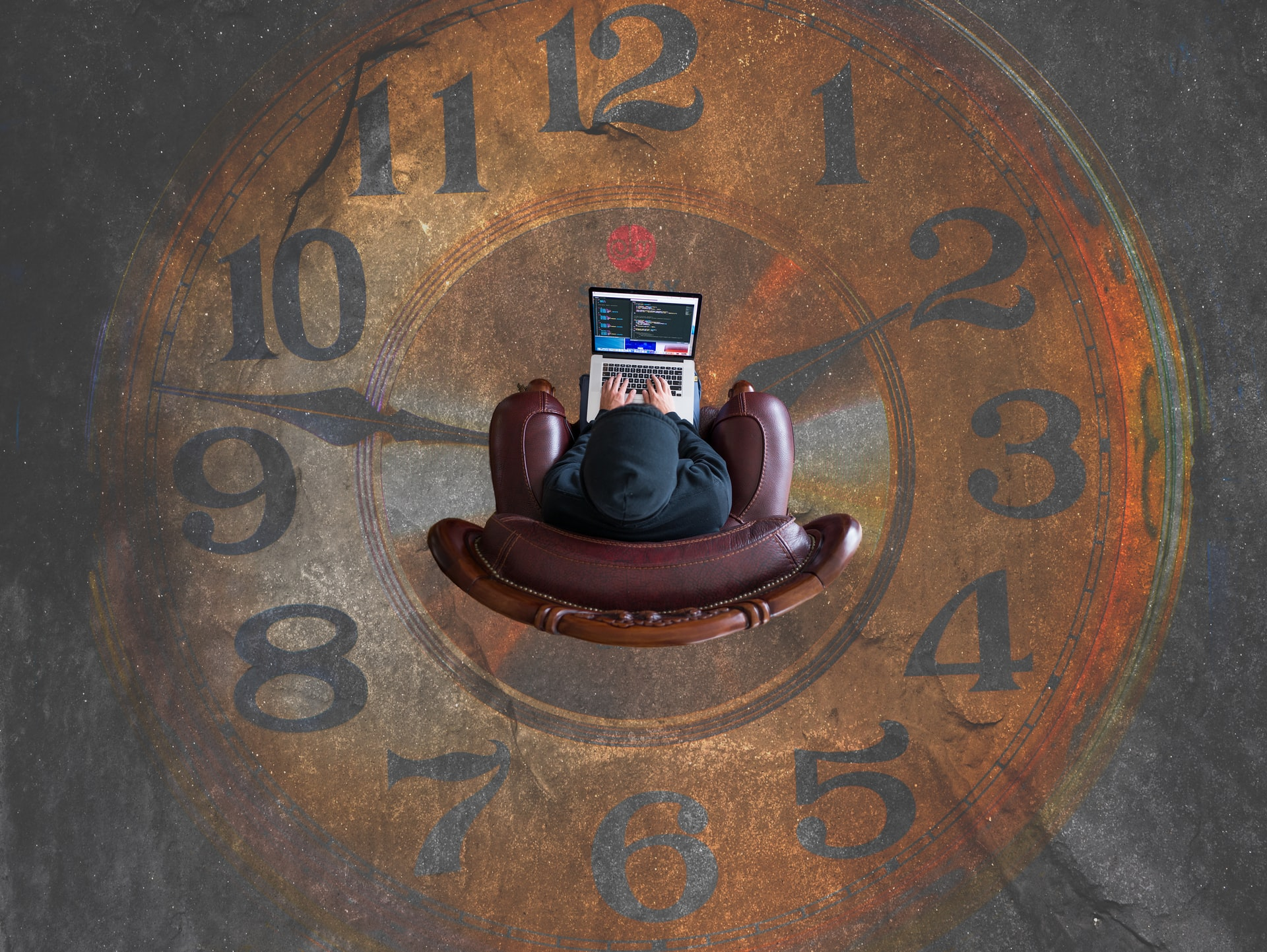 A businessman sitting on a chair, working on a laptop in the middle of a clock, symbolizing that business thrillers and corporate novels with great storytelling are usually not free