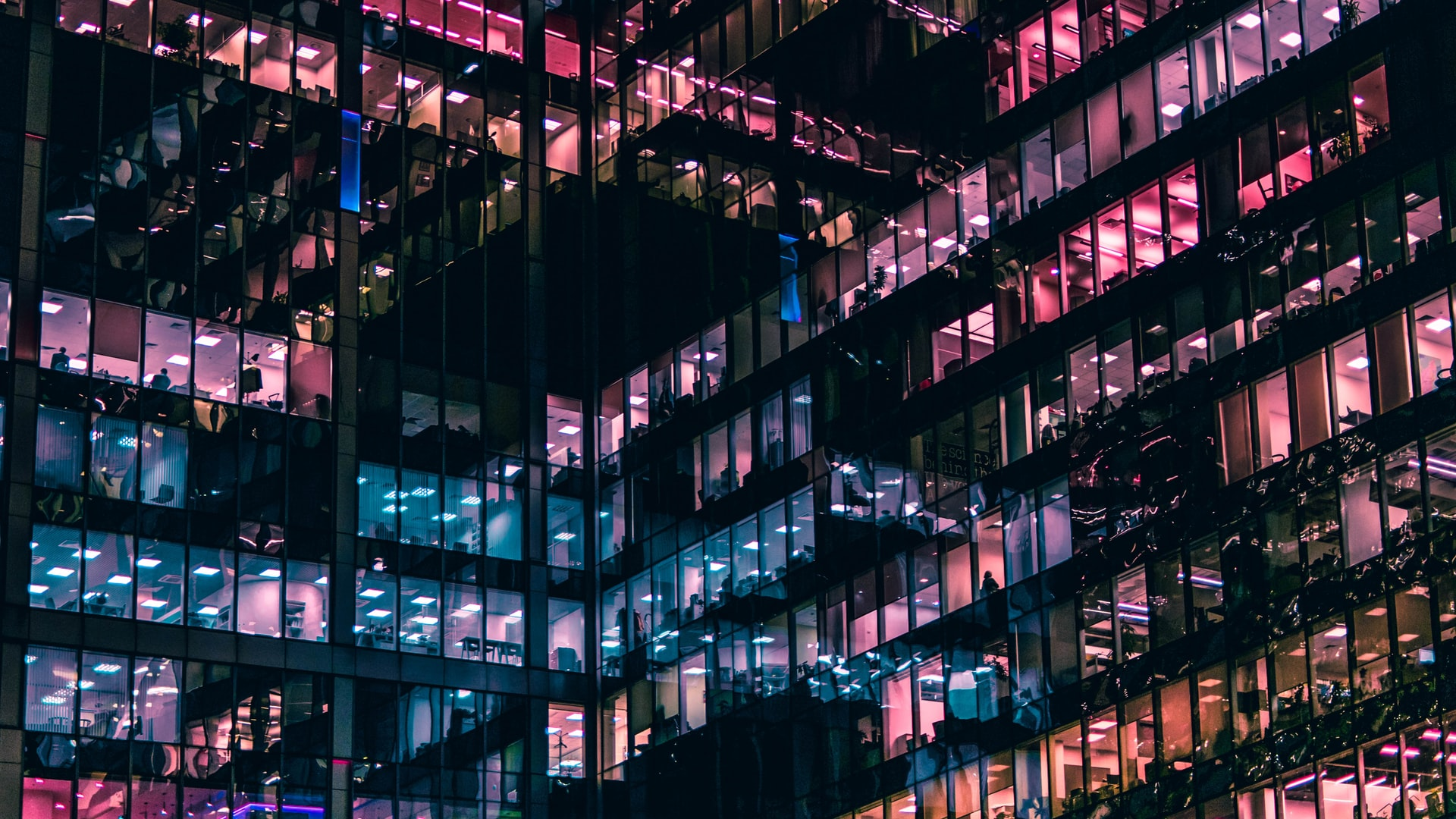 picure of a glass office building by night with pink windows showing managers working on their way up